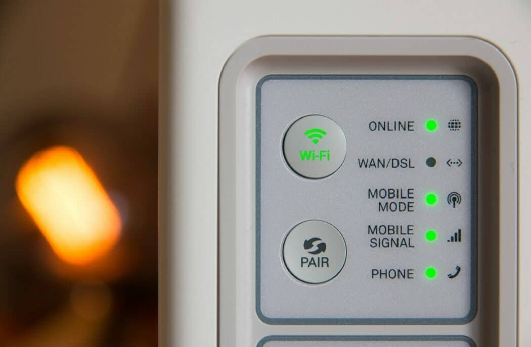 A white modem has various green lights to display its Wi-Fi and phone connection.