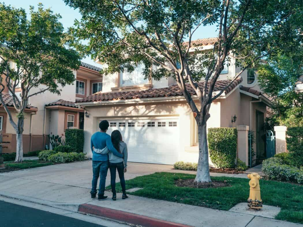 A couple stands outside in front of their home, looking up at the property.