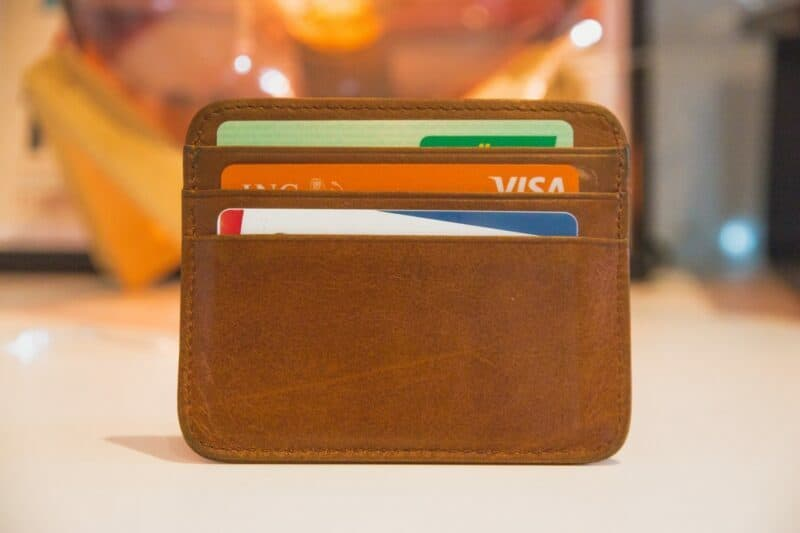 A brown leather wallet displaying credit cards.