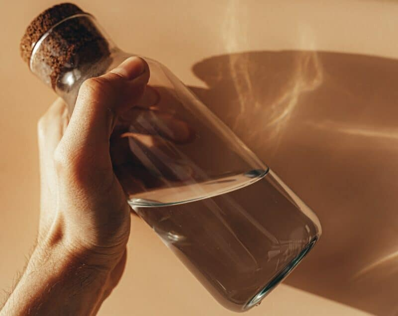 A closeup of a hand holding a glass water bottle in front of a light brown wall.
