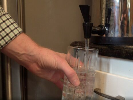 a man filling up a glass of water after using a home water filtration system
