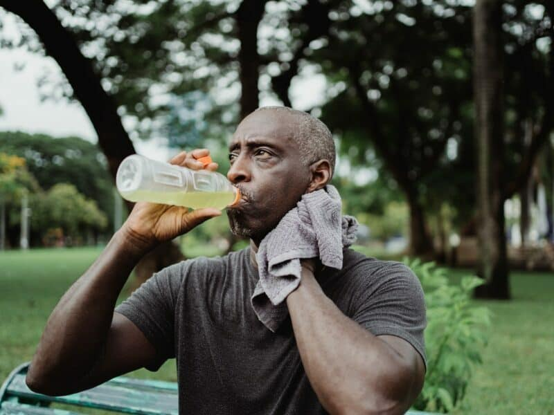 An older man with greying hair is drinking a sports drink while sitting outside in a park.
