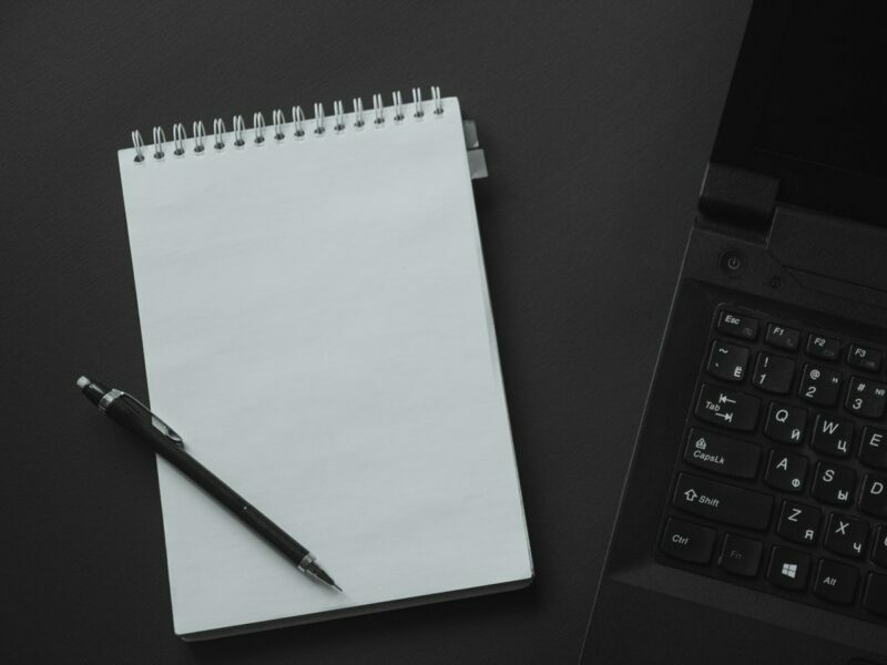 A white notebook with a black pen lying on top of it is next to a black laptop.