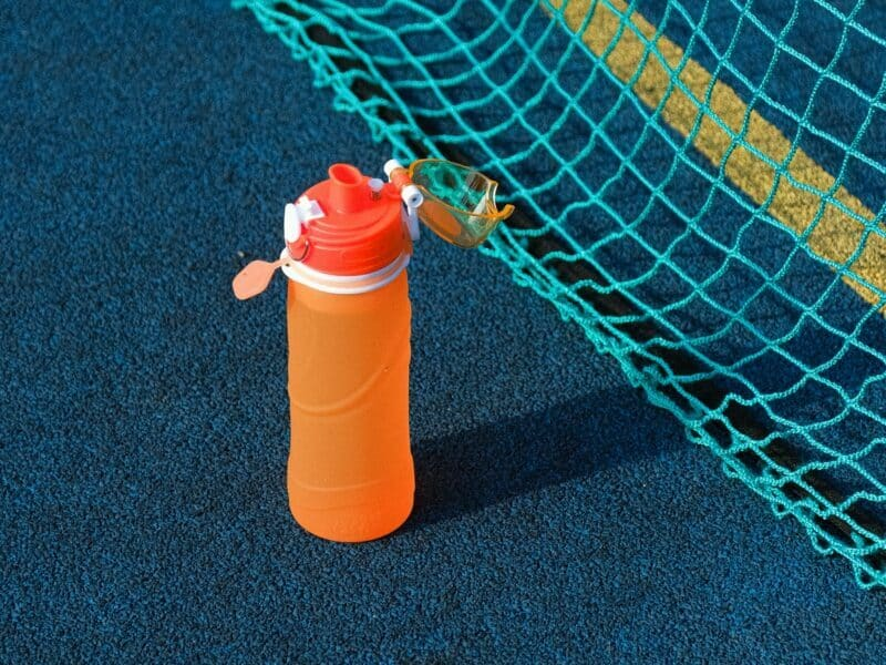 A closeup of an orange reusable water bottle that's on a dark blue tennis court.