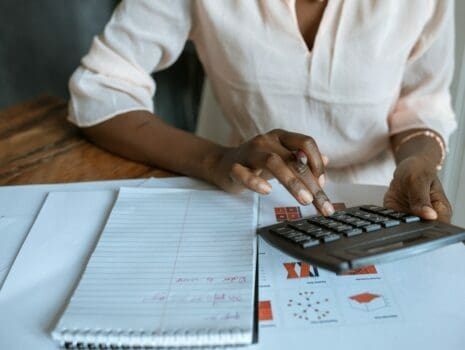 A woman is typing on a calculator while sitting at a table that's holding her notebook and other various documents.