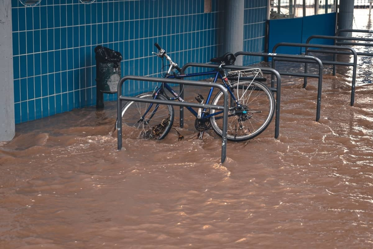 A bike hooked up to a rack is surrounded by floodwater.