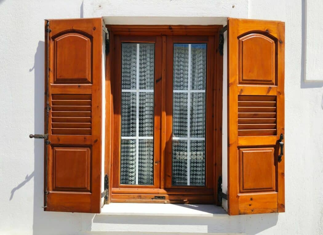 Brown shutters installed on the windows of a white building.