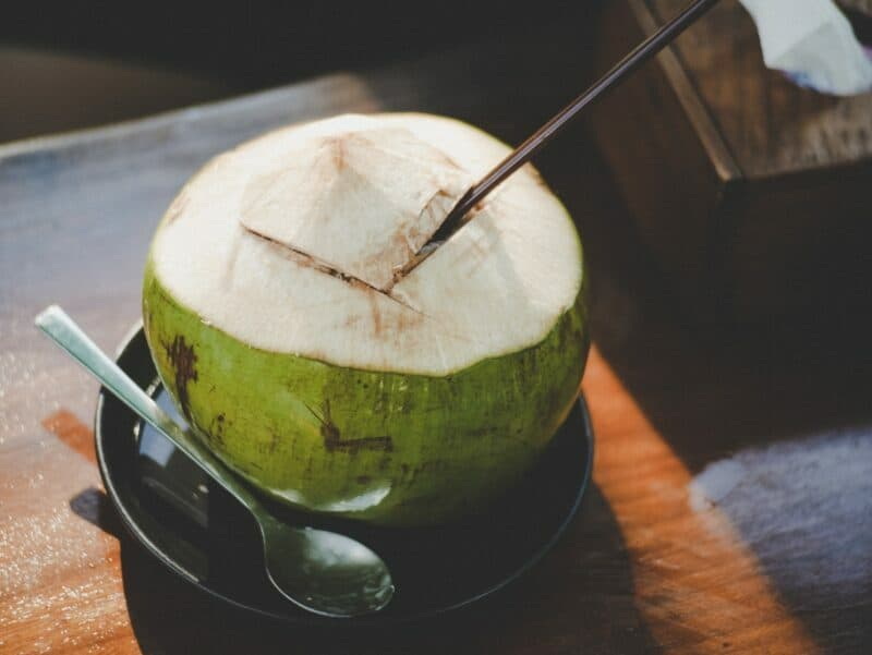a green coconut with a straw to drink coconut water as a post workout drink for hydration