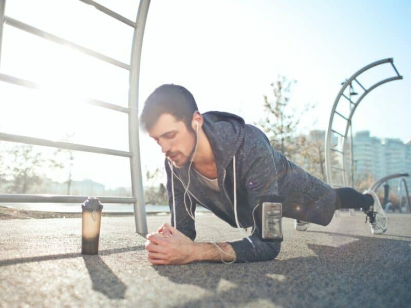 man doing plank workout with a water bottle or shaker bottle next to him