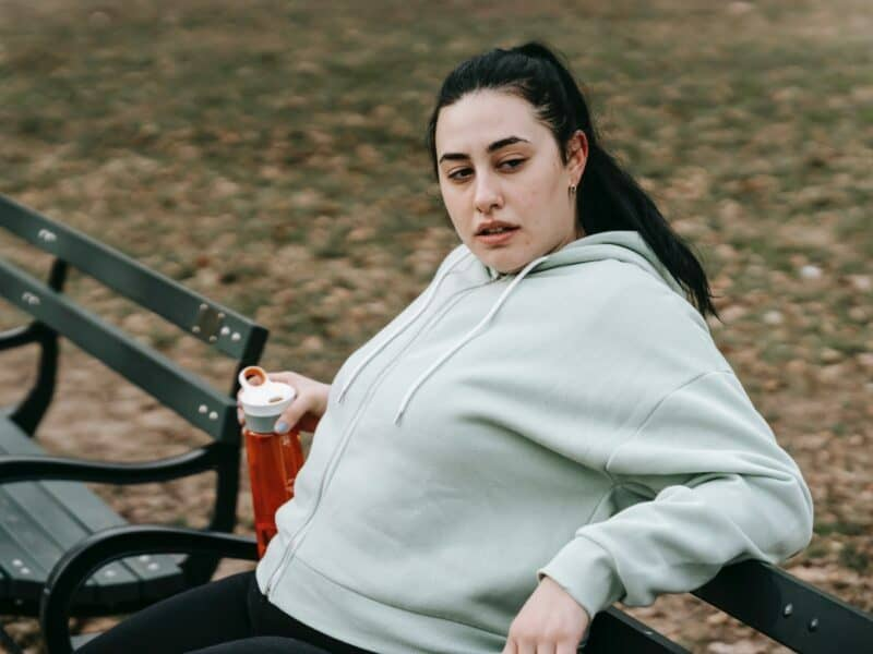 a girl in a gray sweatshirt holding an orange water bottle as a post workout drink