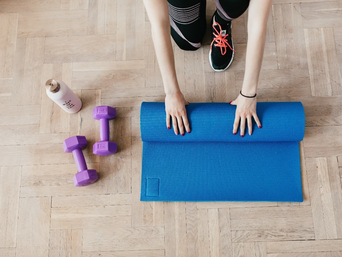 a woman rolling up a blue yoga mat with purple weights and a water bottle