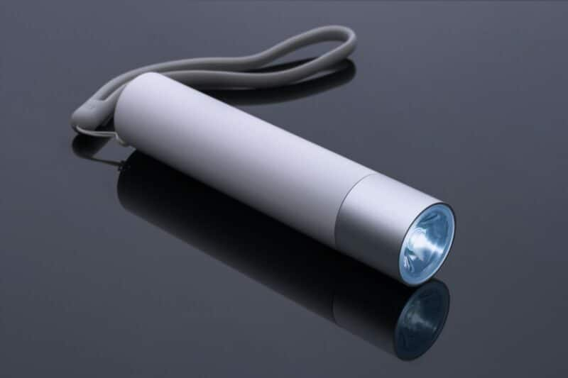 A light grey flashlight is sitting on top of a dark surface.
