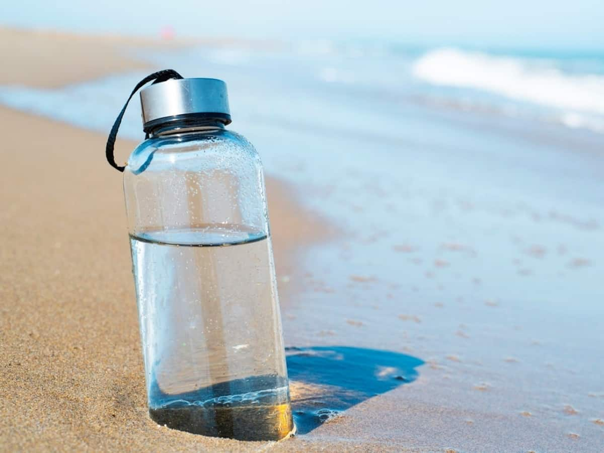 glass water bottle in the sand
