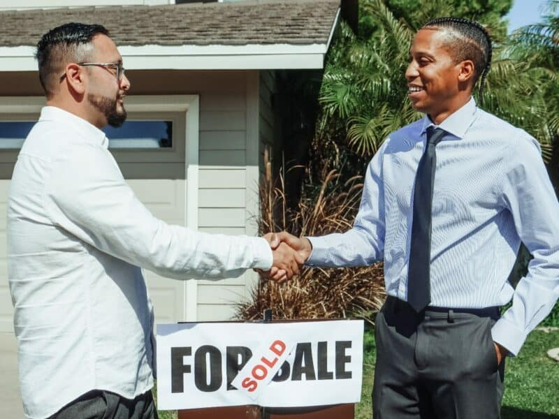 two men standing and shaking hands in front of a for sale and sold sign