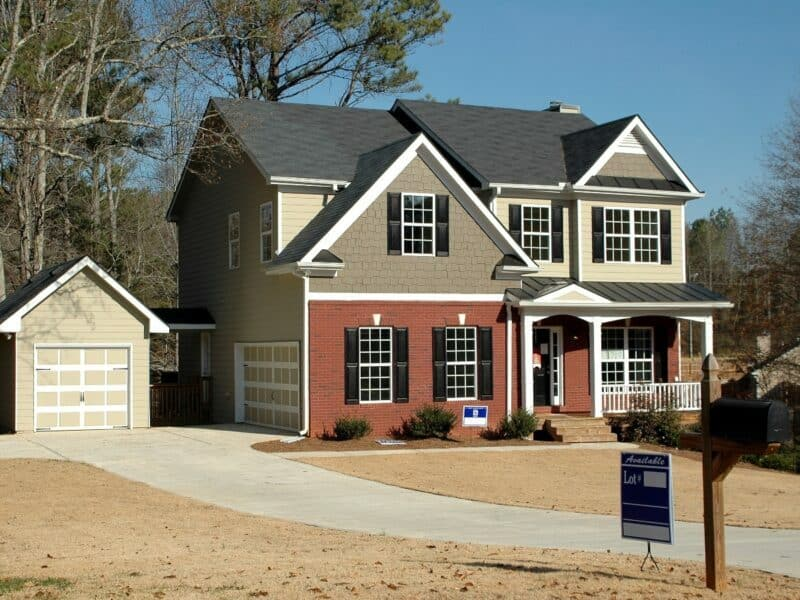 a two story house with detached garage with a for sale sign