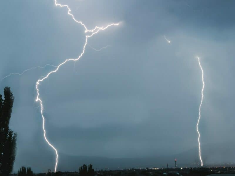 Two lightning bolts striking down onto the ground from a grey sky.