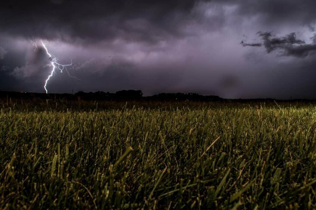Lightning striking down near a field of grass.