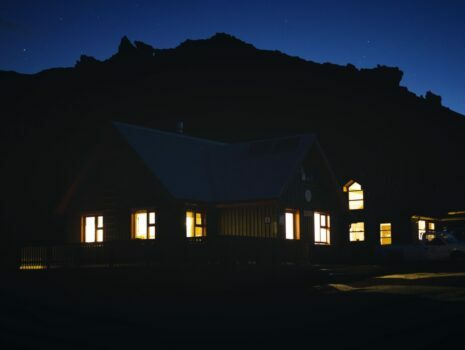 Lights glow from inside of a house at nighttime.