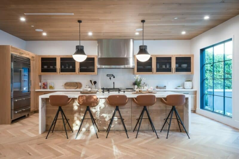 Lights glow inside of a modern kitchen with brown finishes.