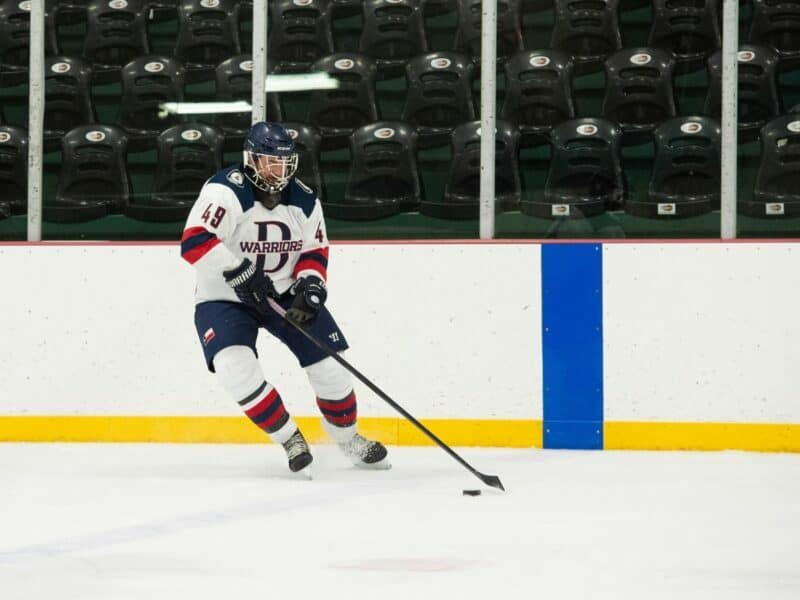 player moving the puck up the ice for the dallas warriors hockey team, a dallas small organization focused on enriching veteran lives