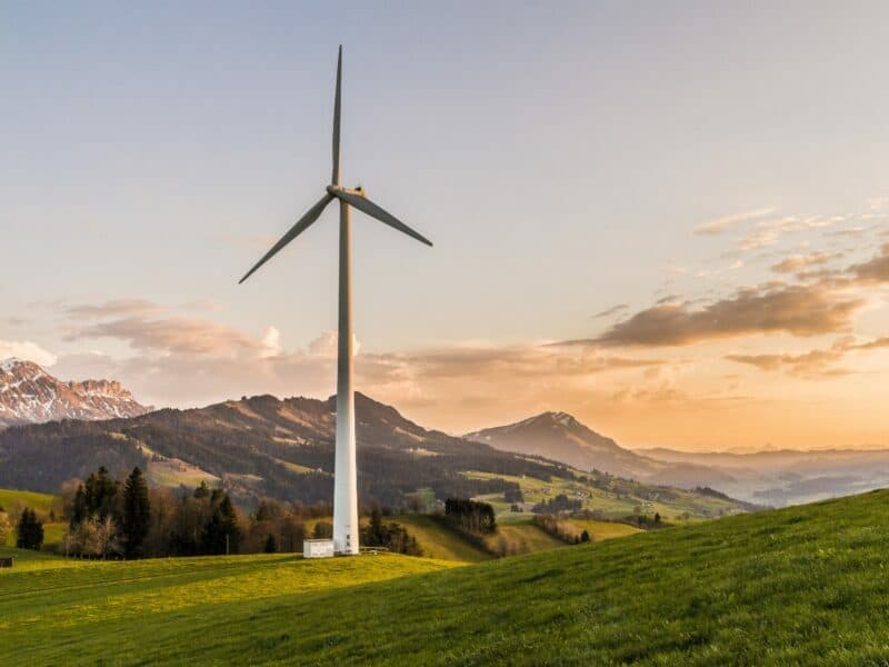 a wind turbine, a form of renewable energy in front of mountain on the coast