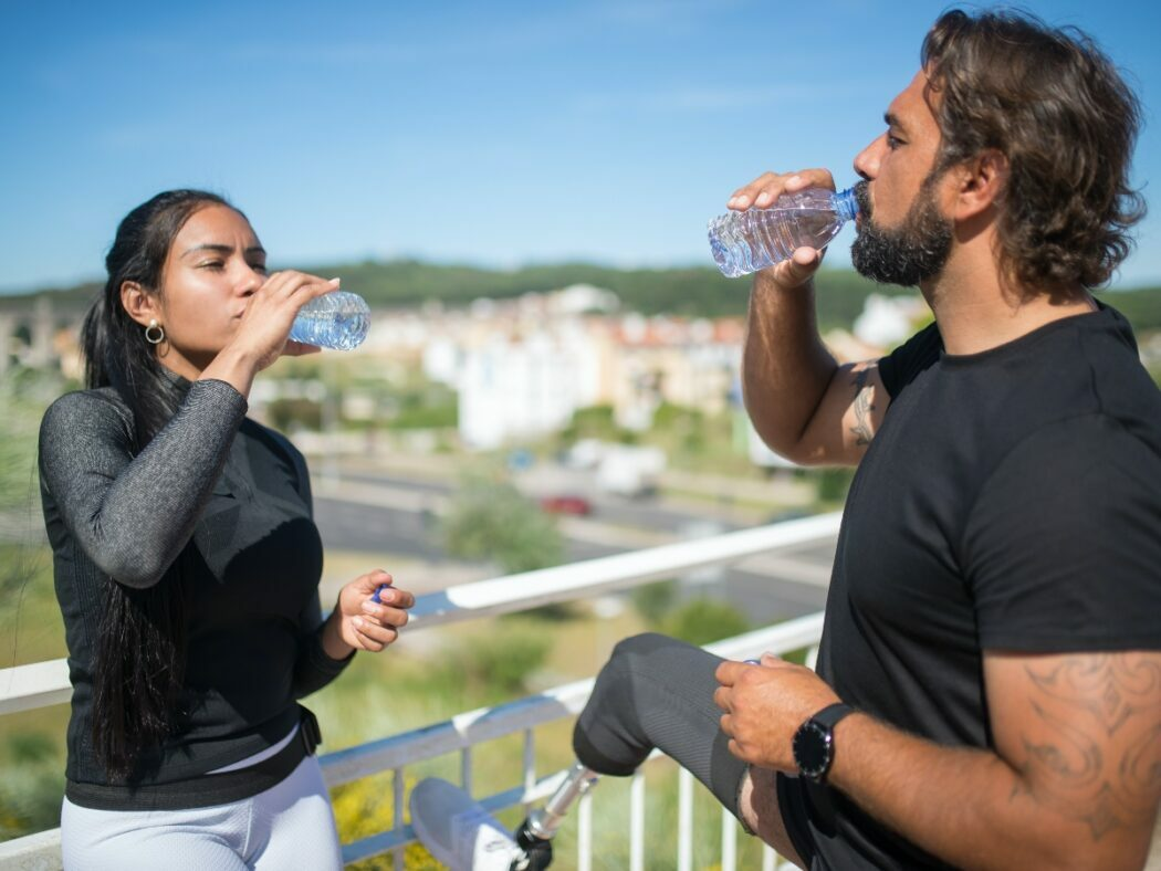 man and woman standing outside drinking water to stay hydrated during the summer