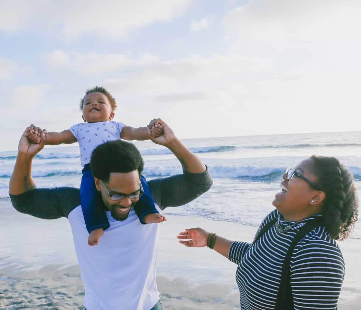A young family is smiling while standing on the beach.