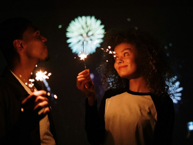 boy and girl hold sparklers with fireworks in the background