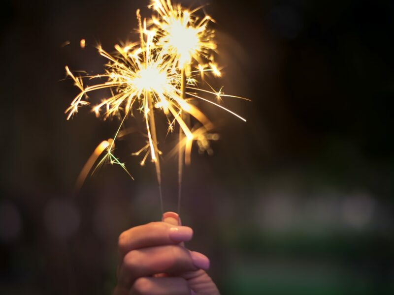a hand holding a sparkler practicing safety