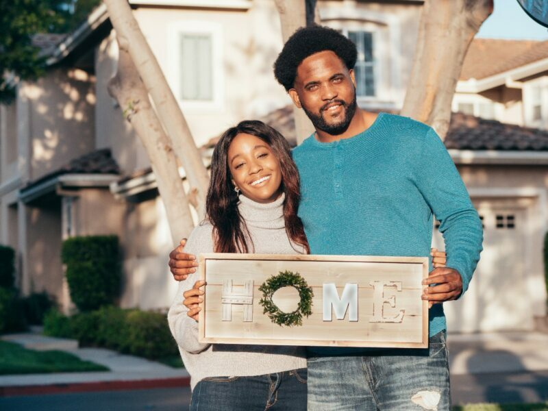"""two new homebuyers standing in front of their new house holding a sign that says """"home"""""""