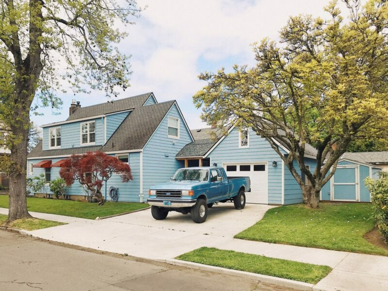 A blue house has a blue pickup truck parked on the driveway.