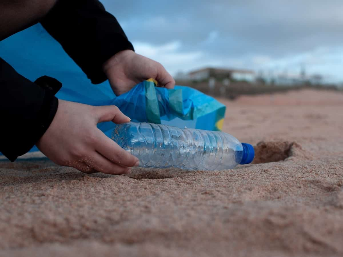 picking up a plastic bottle from the beach to reduce plastic waste and reduce environmental impact