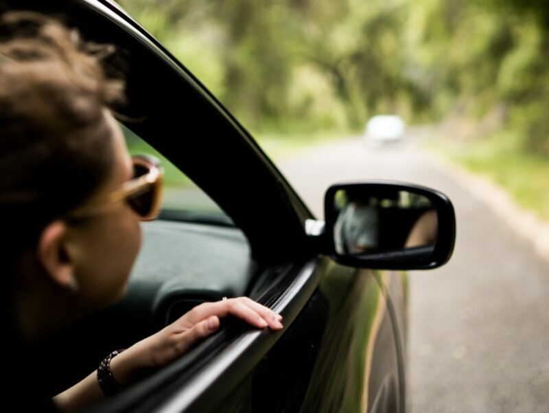 A woman wearing sunglasses has her head out the window while sitting in a car driving down a road that's surrounded by trees.