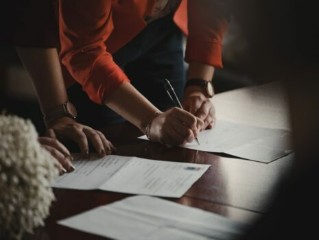 A man and woman in professional clothing are filling out a document.