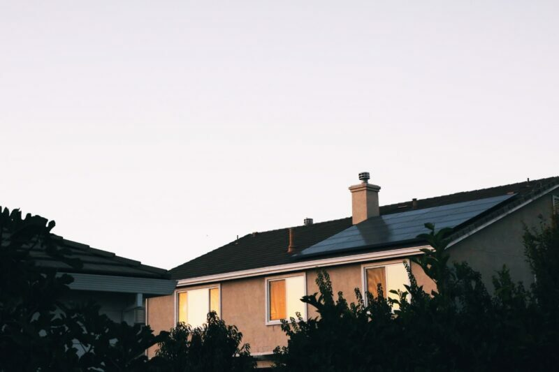 A stucco home with solar panels installed on roof.