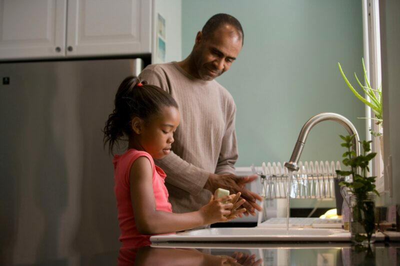 A father teaches his young daughter how to wash her hands at the kitchen sink.