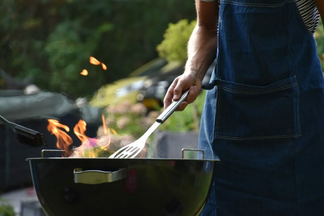 A man holds a spatula close to a black kettle grill outside.