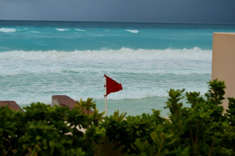 A red flag is waving on a beach to warn about an approaching hurricane.