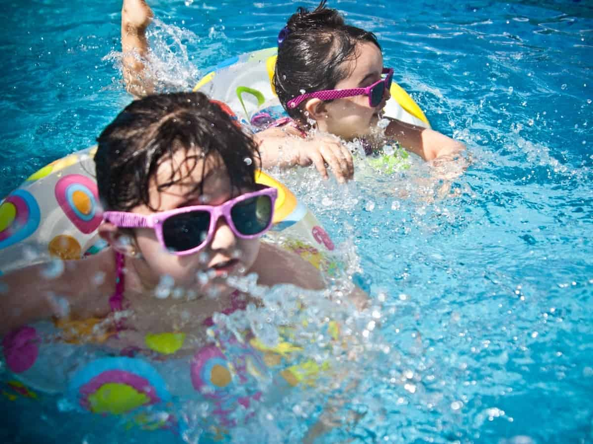 two young girls with sunglasses on in the pool practicing pool safety