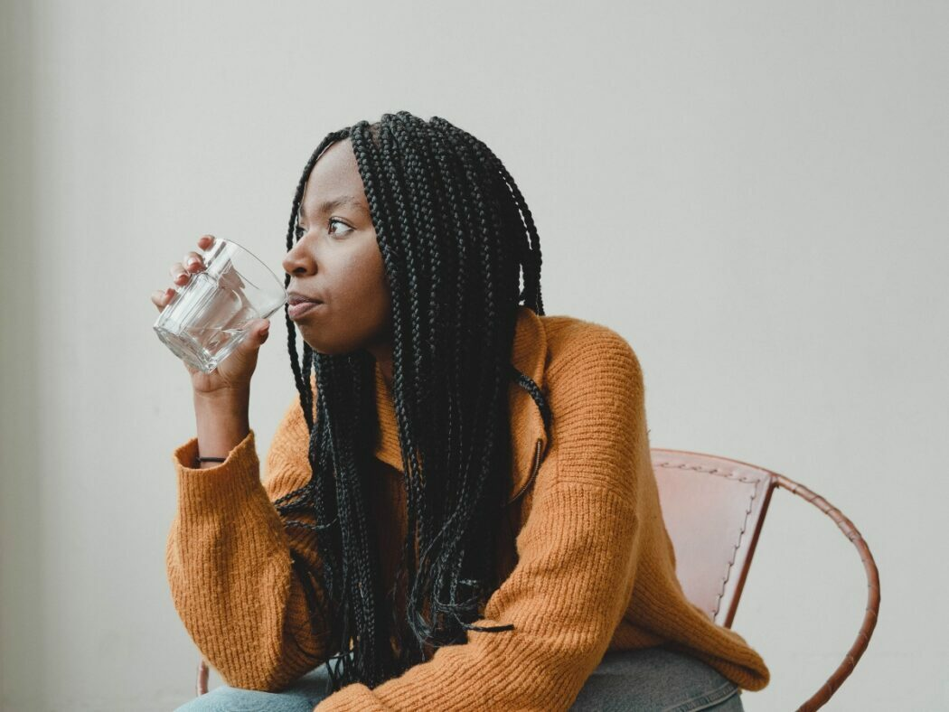 woman drinking a healthiest type of water to drink out of a glass