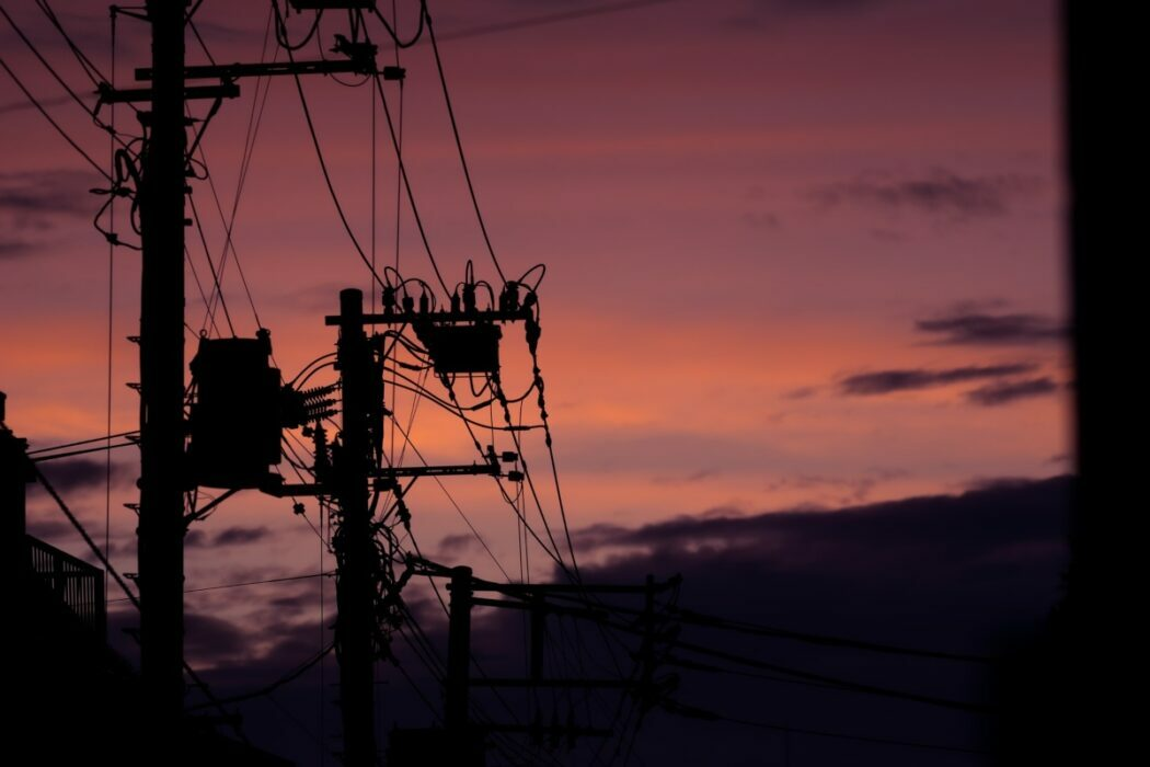Tall power lines standing outside under a pink and purple sky.