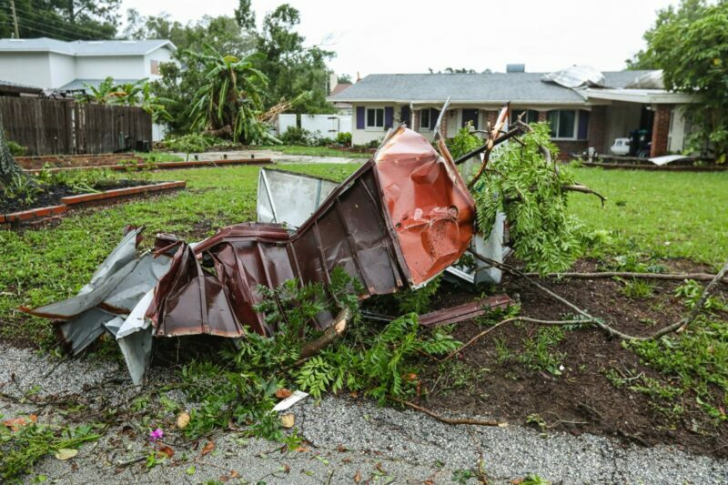 Storm debris lays outside on the front yard of a home.