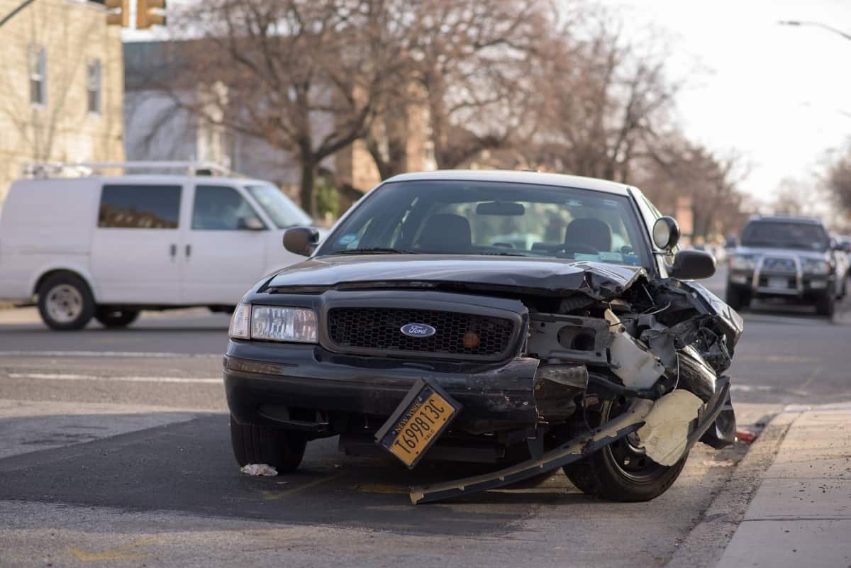 A black car with damage on the driver's side is parked on a road.