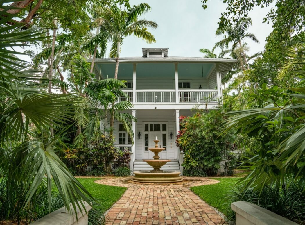 A vacation home in Key West Florida is surrounded by palm trees and other tropical green landscaping.