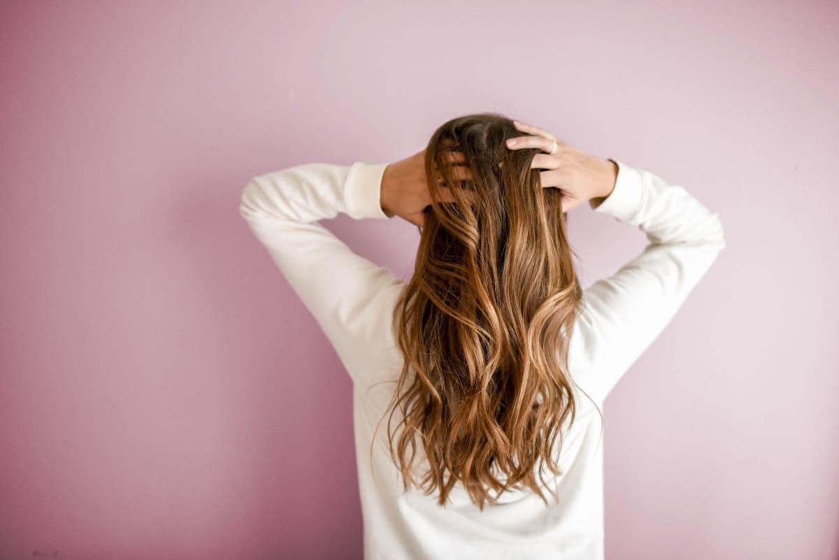 A woman facing a pink wall has long brown hair.