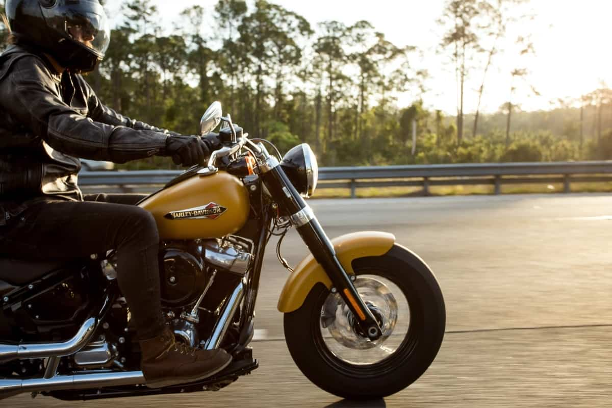 A man wearing a leather jacket, dark jeans, brown boots, and a helmet is riding his motorcycle down a road at sunset.