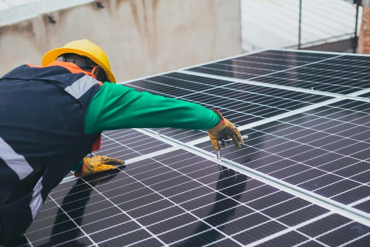 A technician is installing solar panels on the roof of a property.