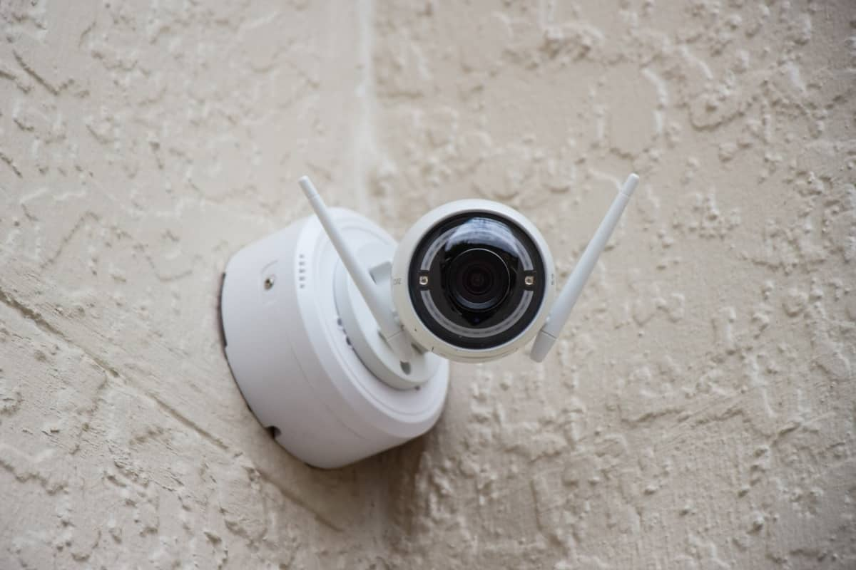 A white video surveillance camera is installed outside on a beige wall.