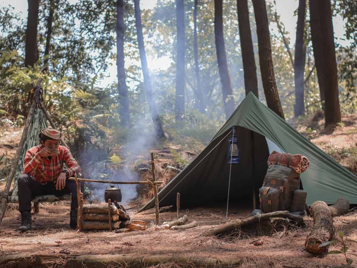 a tent set up with a fire during a camping trip