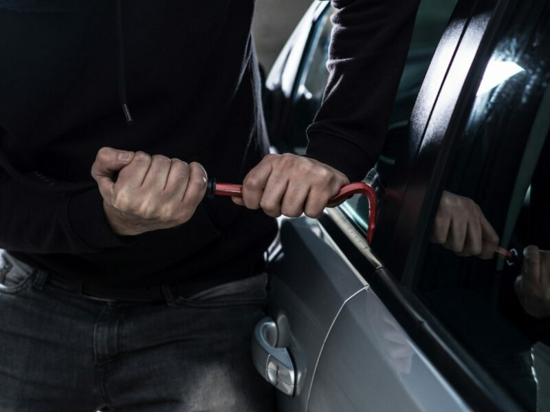 a burglar breaking into a car, breaking the window and vandalizing